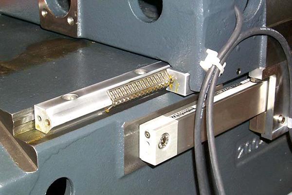 6. ábra: Szikraforgácsoló gép tűgörgős vezetéke, öveg mérőléccel