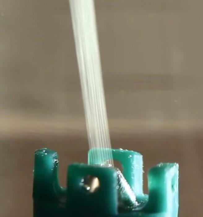 6. ábra Viszkóz előállítása laboratóriumban, nedves szálképzéssel. Látható, hogy a kicsapódás a spinneretet követően gyakorlatilag azonnal megtörténik. (A teljes kísérlet az alábbi videón tekinthető meg: https://www.youtube.com/watch?v=5QFOnZ3TLHQ)